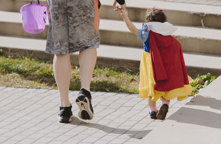 An image of a little girl dressed like Snow White seen from behind. She is holding hands with an adult.