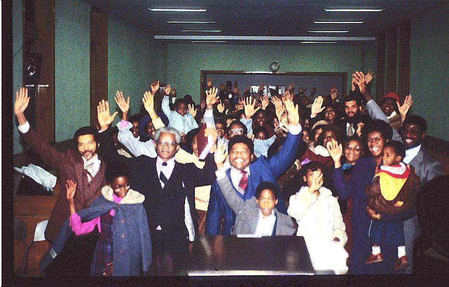 The Pioneers of the New Covenant Church of Philadelphia raise their hands during the very first service.