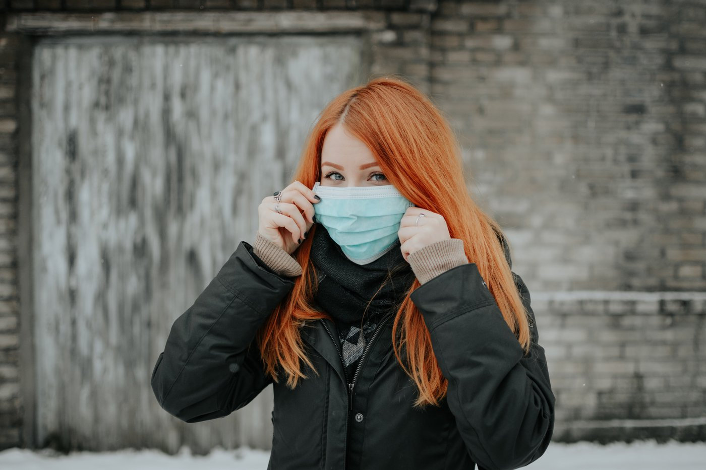 A woman with long red hair holds a face mask over her mouth and nose.